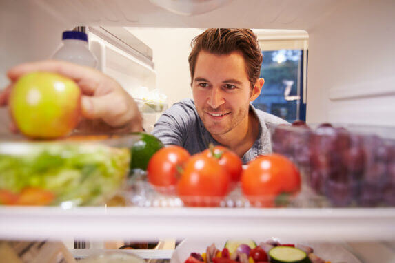 A man grabs an apple from his refrigerator.
